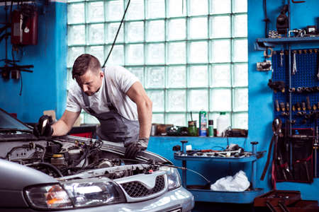 dirty car: Young strong car mechanic at work in shop