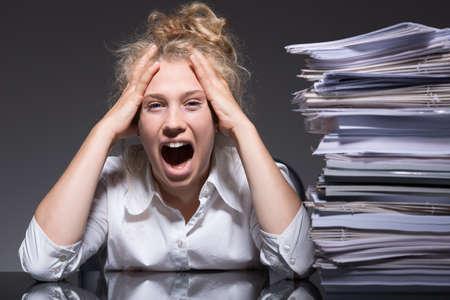 carga: Mujer joven frustrado y estresado en el trabajo Foto de archivo