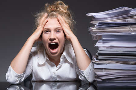 too much: Young woman frustrated and stressed at work Stock Photo