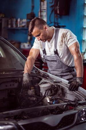 engine bonnet: Focused mechanic looking under car hood Stock Photo