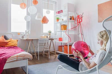 blonde teenage girl: Picture of girl relaxing in modern bedroom