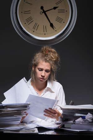 acoso laboral: Mujer trabajadora joven se carga con el papeleo
