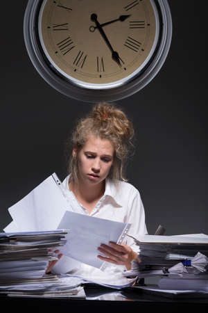 difficult task: Young hard-working woman is loaded with paperwork