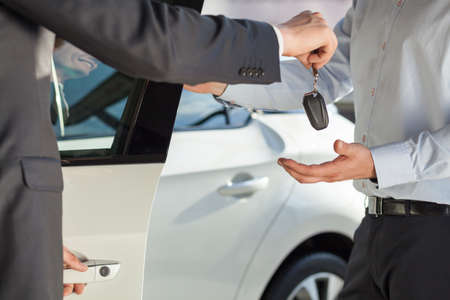 new car: Car dealer is giving a key to the  new car Stock Photo