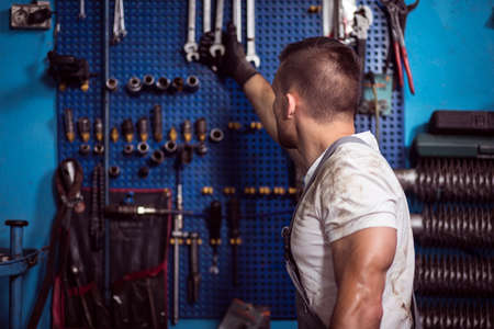 muscled: Muscled car mechanic in uniform reaching for wrench