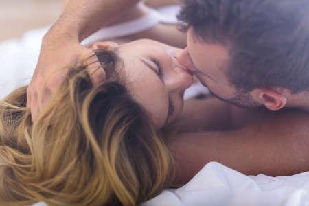 amantes en la cama: Foto de atractiva besos pareja casada en la cama