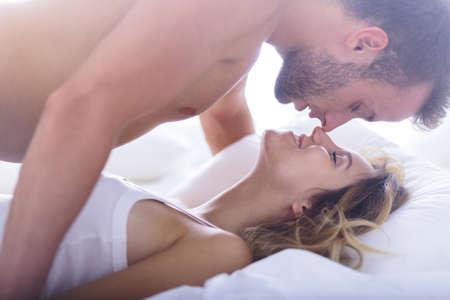 enamorados en la cama: Foto de atractiva rompecorazones y su amante sexy