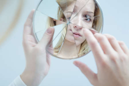 on mirrors: Insecure pretty young woman holding broken mirror