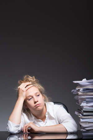 heartsick: Young overworked emploee has lots of paperwork Stock Photo