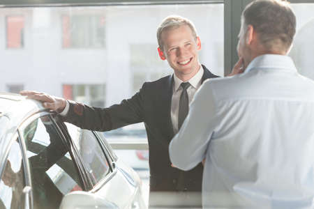 salesperson: Car salesperson is smiling to his client