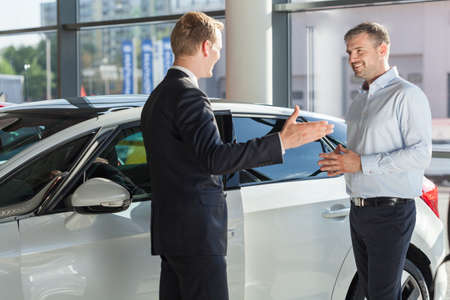 car salesperson: Customer is smiling to his car dealer