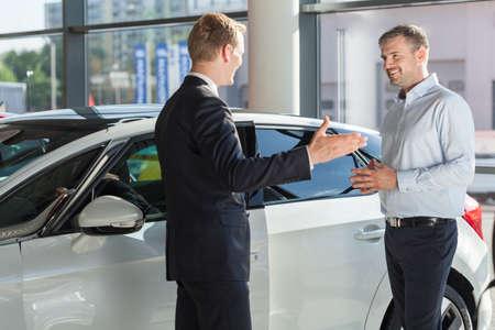 Klant glimlacht naar zijn auto dealer Stockfoto