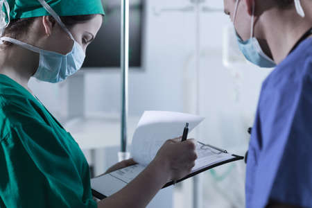 anesthesiologist: Image of anesthesiologist and surgeon discussing conditions for narcosis