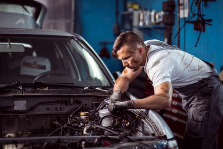 dirty car: Young dirty mechanic working in car repair shop Stock Photo