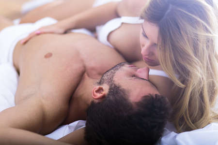 amantes en la cama: Imagen de la mujer romántica tocar su novio deportivo