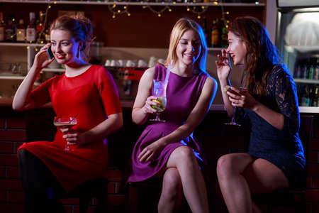 chicas sonriendo: Las ni�as hablando y bebiendo en el bar