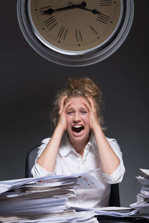 Young overworked woman is frustrated because of work
