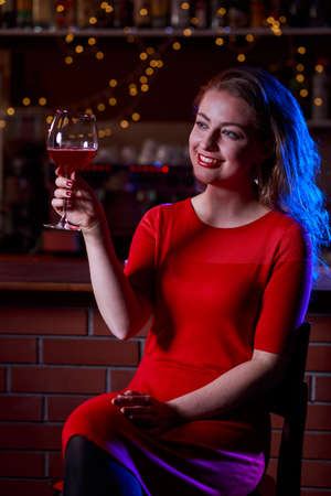 sexy dress: Elegant woman in red dress with a glass of wine
