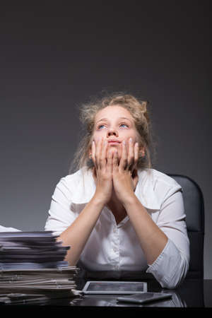 jaded: Young totally burnout woman at work place Stock Photo