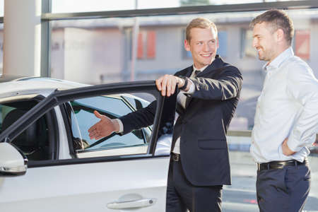 open car door: Car dealer is presenting inside of the car Stock Photo
