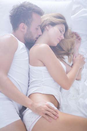 enamorados en la cama: Imagen de una pareja rom�ntica de enamorados tumbado en la cama