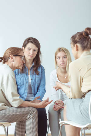terapia de grupo: Mujer joven confiando problema a su grupo de apoyo