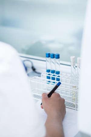 describing: Young scientist is describing new samples, vertical
