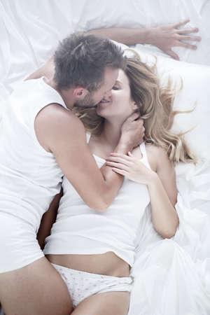 Beeld van paar tijdens gepassioneerde voorspel in bed Stockfoto
