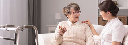 Senior older woman talking with female young caregiver Stockfoto