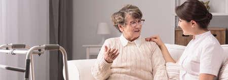 Senior older woman talking with female young caregiver Foto de archivo