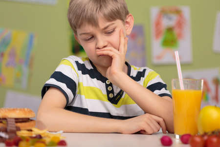 obesity kids: Image of child with grimace dislike healthy lunch Stock Photo