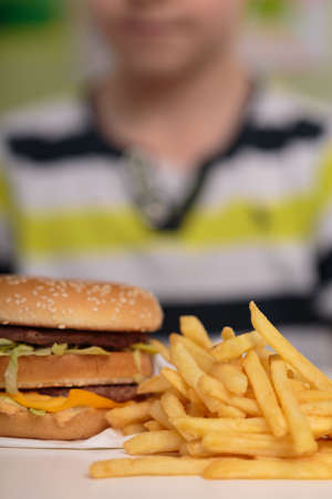 fastfood: Image of boy and unhealthy caloric junk food