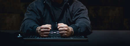handcuffs: Angry man in handcuffs in front of computer Stock Photo