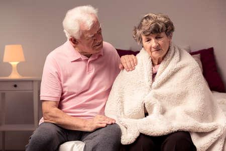 Immagine di uomo che aiuta moglie triste con afflizioni di salute
