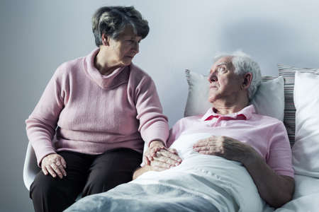 Image of helpful woman visiting old man at hospice