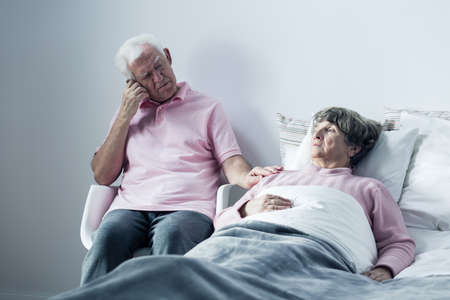 mortally: Image of husband supporting mortally ill old wife Stock Photo