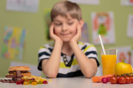 obesity kids: Image of boy and choice between healthy and unhealthy food