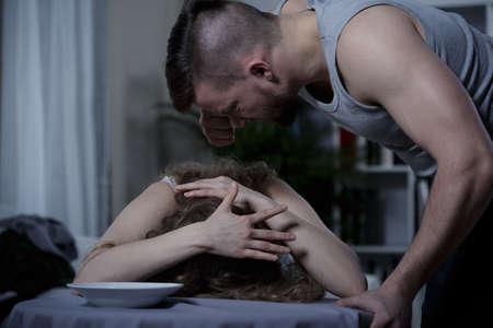asustado: Hombre violento joven gritando a la mujer asustada