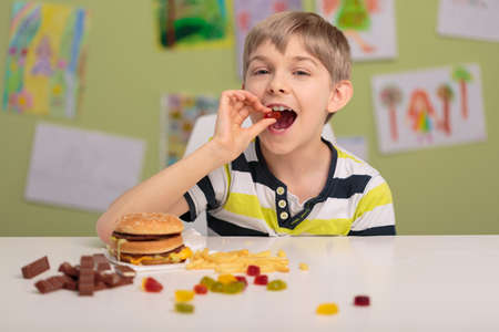 Photo of content child eating sweets and fastfood Stock Photo