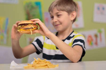 niños comiendo: Foto del niño con apetito por la grasa y calorías hamburguesa