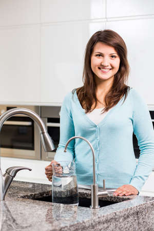 Beeld van gelukkige meisje met een kruik kraan water Stockfoto