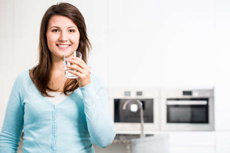 people drinking water: Image of young woman with glass of tap water