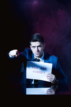 you are fired: Image of boss holding card with writing you are fired