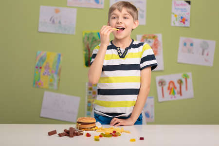 addicted: Image of small boy addicted to fastfood and sweets