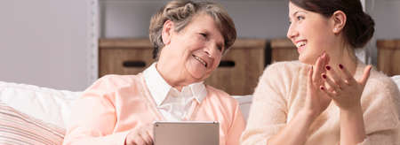 caring: Older happy woman and new wireless technology Stock Photo