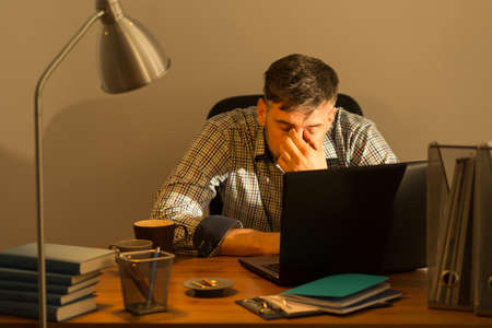 Mature man working late hours at home