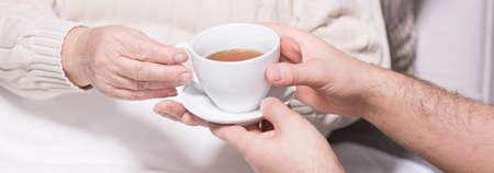 personas ayudando: Primer plano del hombre servir el té caliente para mujer mayor