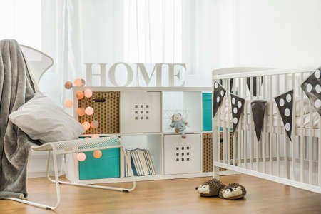 stylish boy: Crib and commode in cozy baby room Stock Photo
