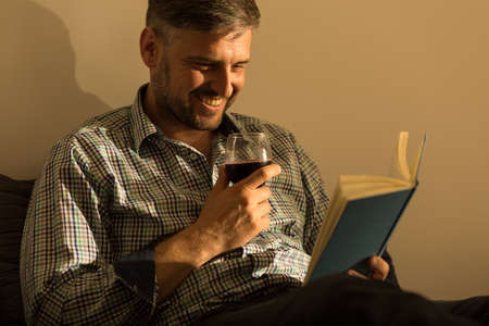interesting: Smiling man reading interesting book in bed Stock Photo