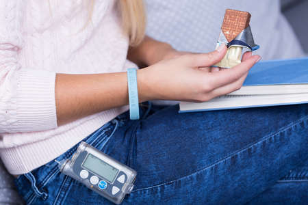 a bracelet: Close-up of ill diabetic woman eating sweets Stock Photo
